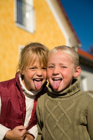 Sisters sticking their tongue out at the viewer Stock Photo