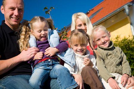 trois enfants: Une jeune famille avec trois enfants devant leur nouvelle maison assis dans le soleil