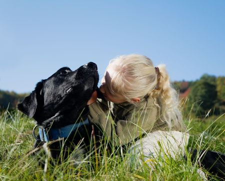 A girl whispering a secret in her dog�s ear photo