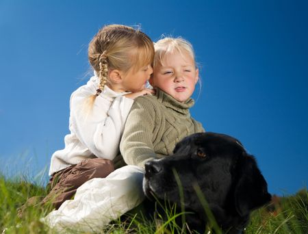 untroubled: Girl whispering a secret in her sister's ear, both sitting upon their (very patient) dog Stock Photo