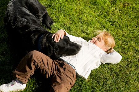 untroubled: Totally relaxed Little girl and her dog having a nap on the lawn in the sun