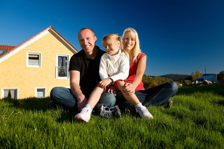 Young family sitting in the sun on the lawn in front of their new home Stock Photo - 3380359