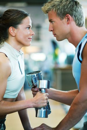 Two people (male / female) lifting dumbbells, shallow depth of field A couple in the gym, rivaling each other, exercising with weights Stock Photo - 3422982