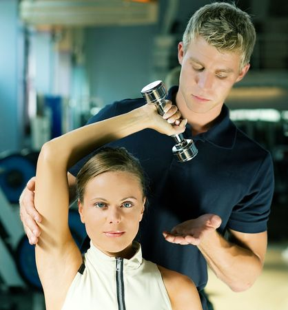 Young woman lifting a dumb-bell in the gym assisted by her personal trainer photo