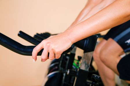 static bike: People using stationary bike in a gym (no faces to be seen) Stock Photo