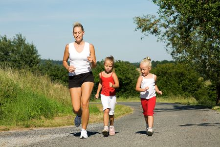 A young mom running with two daughters