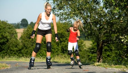 roller skates: A young mother roller skating with her daughter