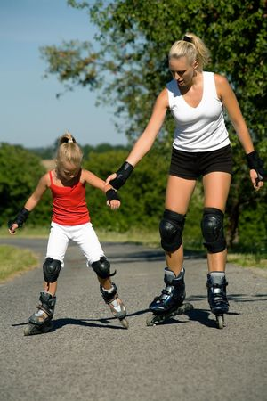 Mother helping her daughter learning to skate photo