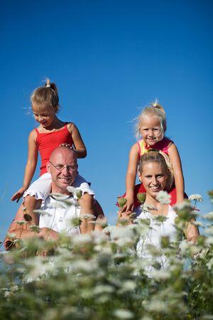 ni�o abrigado: Una joven familia con dos hijas cute sentado sobre los hombros de los padres, esto en un campo de Yarrow  Foto de archivo