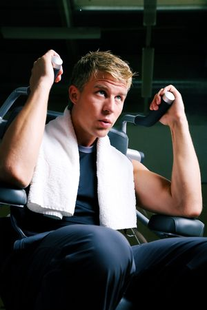 quite: Man pushing the dumbbell-machine in a gym quite hard