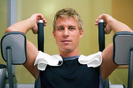 having a break: Man at the machine in a gym having a break