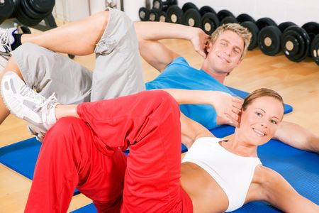 warming up: Couple with brightly colored clothes doing sit-ups in the gym Stock Photo