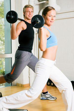 Sehr attraktiv und sportlich Paar tun Macht Gymnastik mit Barbells