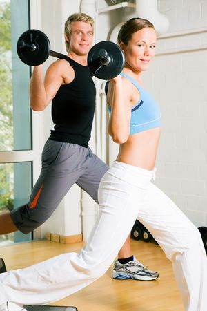 Very attractive and sportive couple doing power gymnastics with barbells photo