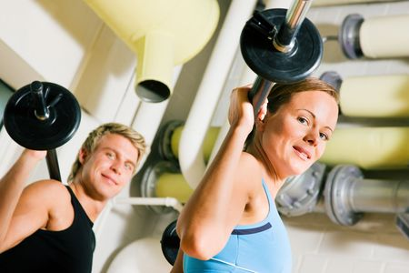 synchronously: Very attractive and sportive couple doing power gymnastics with barbells