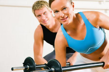 Very attractive and sportive couple doing power gymnastics with barbells Stock Photo - 3555036