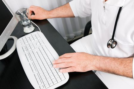 Medical Doctor (only hands to be seen) doing administrative stuff at his computer photo