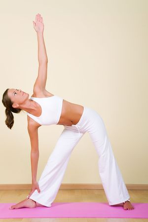 trikonasana: Young woman in a yoga position (Utthita Trikonasana) Stock Photo