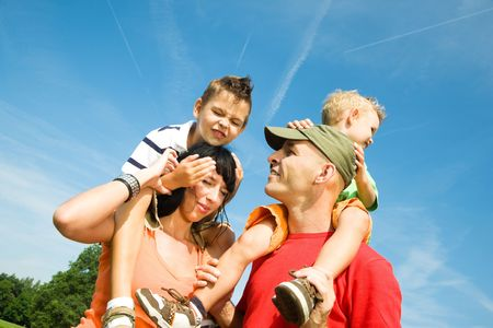 sheltered: Family carrying their two sons on their shoulders under a perfect sky Stock Photo