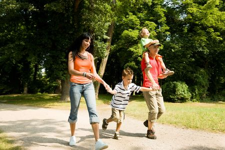 romp: Family with two kids having a walk in the park (focus is on the boy in front!)