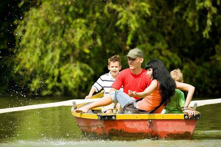 Family with two kids having a boat trip, a lot of water drops in the air (focus on the mother, shallow depth of field) Stock Photo