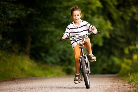 Little Boy riding his bicycle on a dirt road photo