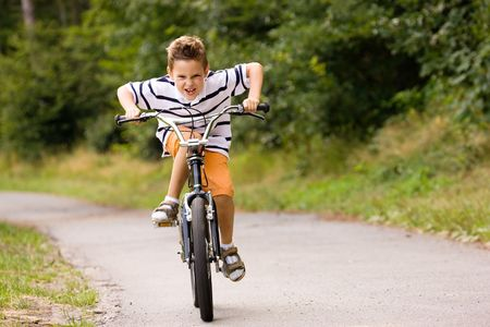 Little boy being really fast on his bicycle photo