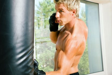 Boxer hitting the sandbag hard Stock Photo - 3555157