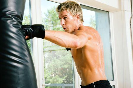 Boxer hitting the sandbag hard Stock Photo