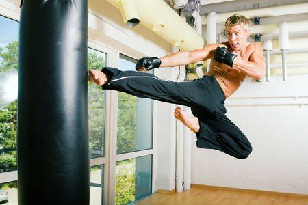 artes marciales: Kickboxer realmente volando a los sacos; un ligero desenfoque de movimiento visible