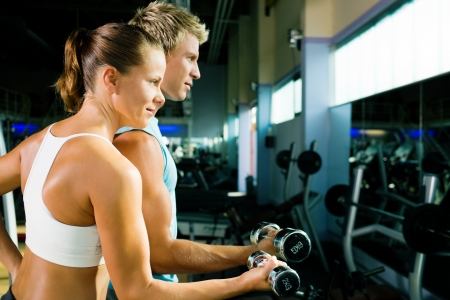 couple in the gym, rivaling each other, exercising with weights (focus on the face of the girl) photo