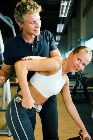 assisted: Young woman lifting a dumbbell in the gym assisted by her personal trainer