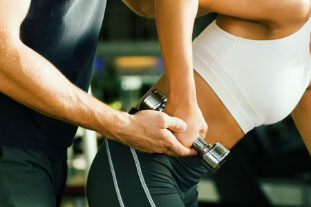 athletics training: Young woman lifting a dumbbell in the gym assisted by her personal trainer (Close-up, no faces to be seen) Stock Photo