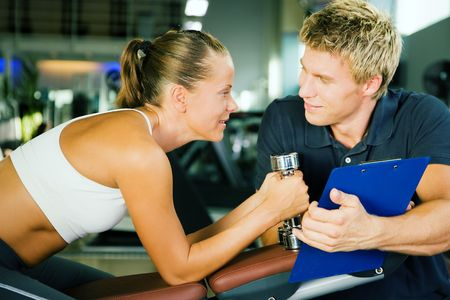 gives: Woman with dumbbells in a gym, her personal trainer gives a report on her training