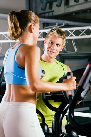 he and she: Couple in a gym, she is working out on a cross trainer, he is looking at her and could be her personal trainer supervising her training