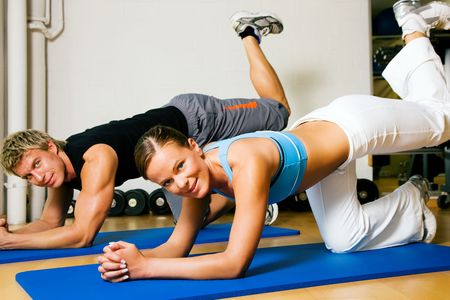 might: Couple in a gym performing gymnastics that are supposed to make a sexy lower back. Judging from the models it might work. Stock Photo