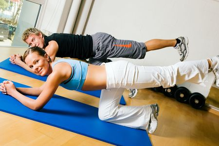 Couple in a gym performing gymnastics that are supposed to make a sexy lower back. Judging from the models it might work. photo