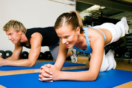 judging: Couple in a gym performing gymnastics that are supposed to make a sexy lower back. Judging from the models it might work. Stock Photo