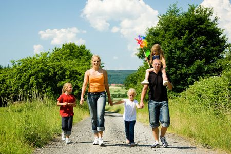 Happy family walking down a path on a bright summer day photo