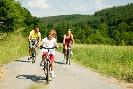 Family with one child riding their bicycles on a summer day (focus on the girl in front) Stock Photo - 3614327