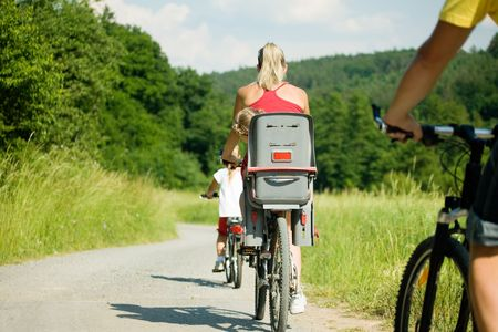 Family with two kids riding their bicycles on a summer day (seen from behind) Stock Photo - 3614324