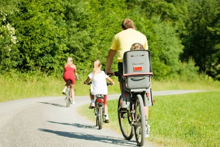 Family with two kids riding their bicycles on a summer day (seen from behind) Stock Photo - 3614323