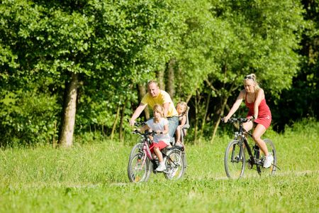 Family with two kids riding their bicycles on a summer day Stock Photo - 3614322