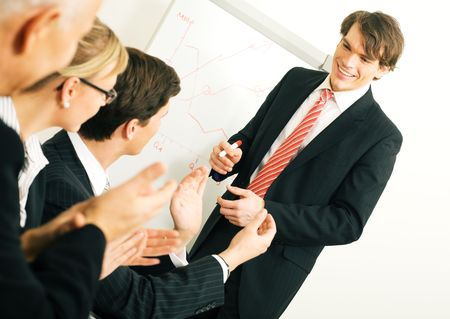 Business team applauding after a successful business presentation (selective focus only on the presenter!) photo