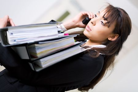 simultaneously: An unhappy female office employee carrying files and using cell phone simultaneously