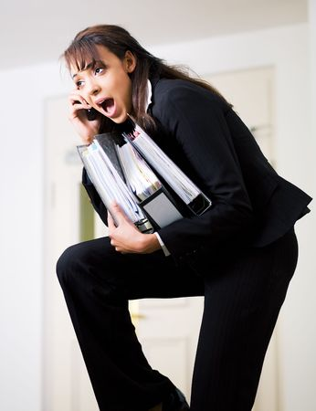 simultaneous: Female office worker being barely able to do all assigned tasks simultaneously Stock Photo