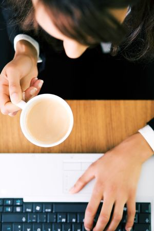 A woman (just hands and parts of face) at her workplace having a double espresso (focus on hand and cup) photo