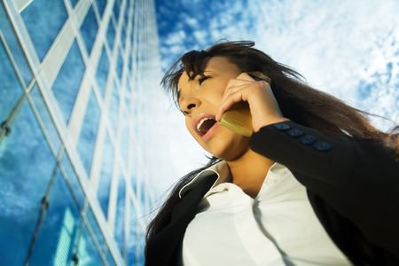 A young brunette professional using her cell phone, shouting at it or receiving not so good news photo