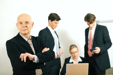 business team with a portrait of the very confident team leader in foreground (selective focus only on the team leader!) Stock Photo - 6094217