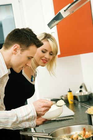 Young couple cooking in their kitchen at home. Selective focus on his face and cooking gear photo